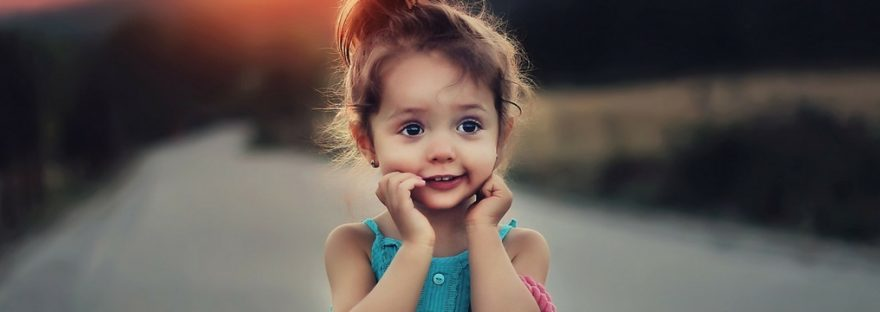 Niña soriente, perpleja y de apariencia feliz